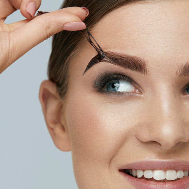 woman peeling eyebrow tint from her eyebrow