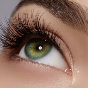 a green eye with lash extensions
